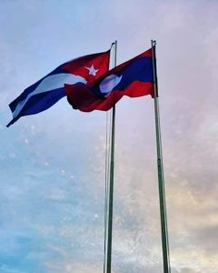 Flags of Laos and Cuba fly over That Luang Esplanade