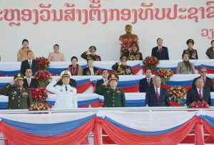 Presidents of the Lao PDR present and former standing to attention as military leaders salute.